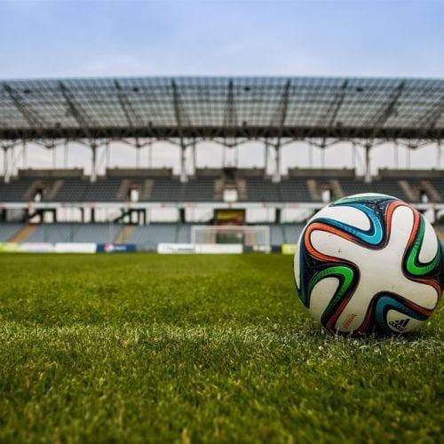 Naming en el fútbol con balon en el centro de un estadio