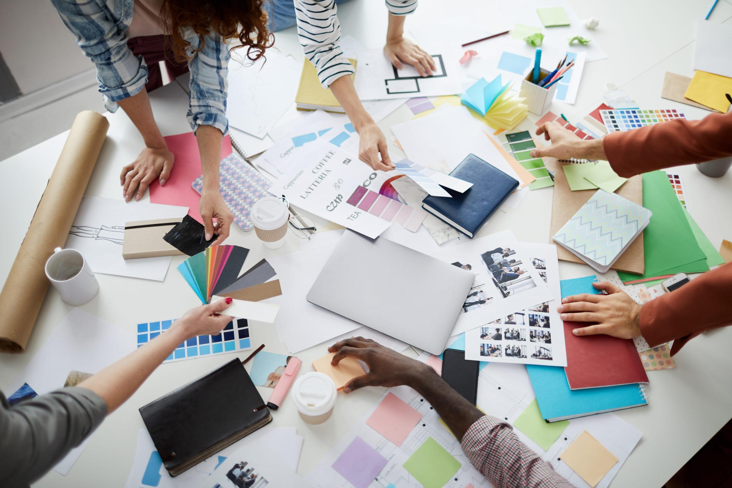 equipo de personas sobre mesa de trabajo con papeles