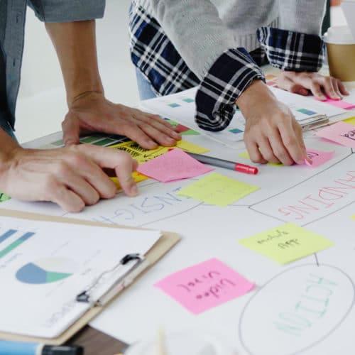 manos y postits sobre mesa en un taller de branding