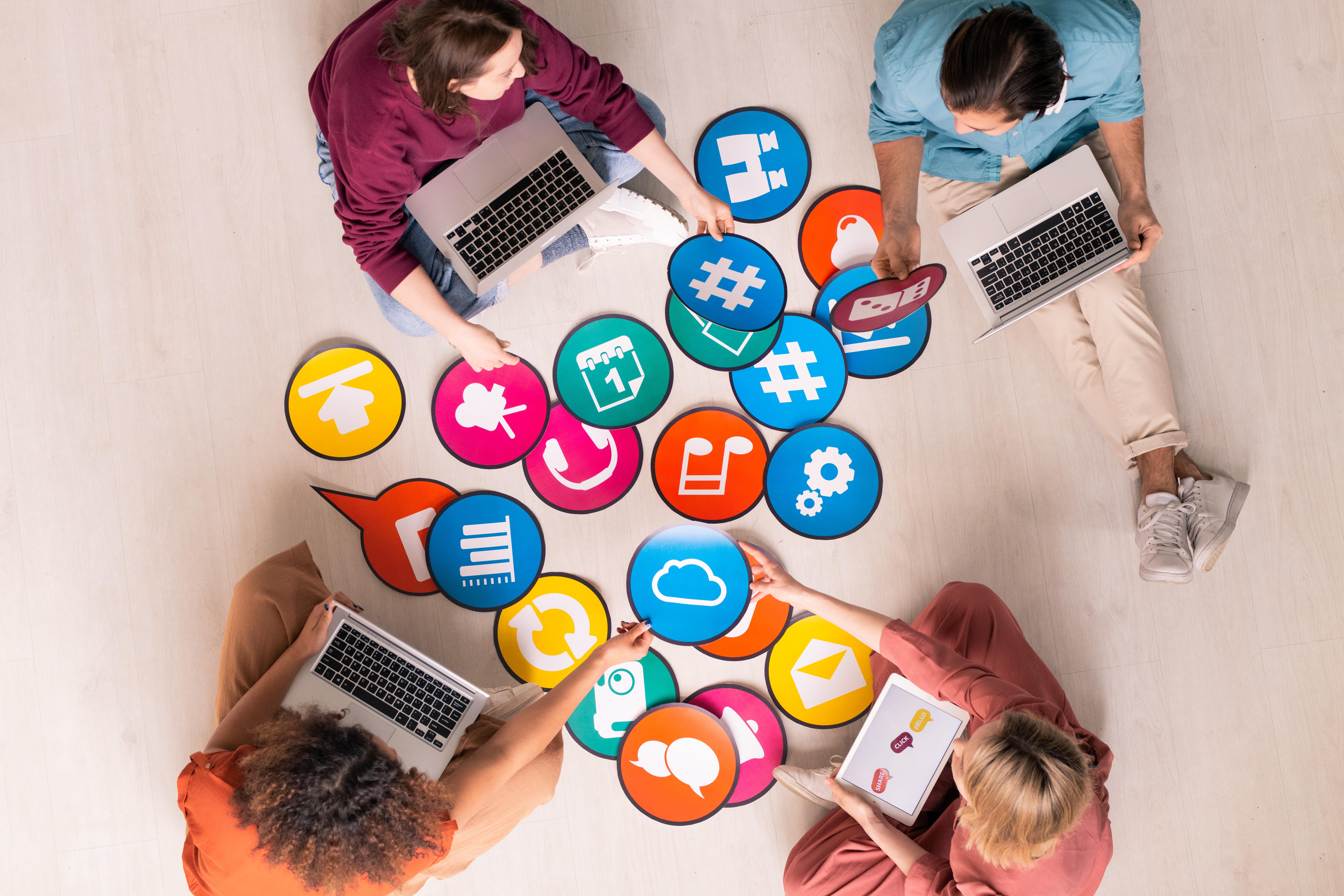 persoans con ordenadores e iconos de marketing digital